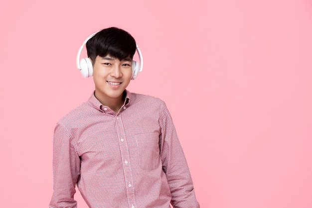 Bonito homem asiático sorridente usando fones de ouvido, ouvindo música