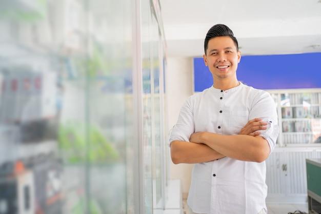 Bonito homem asiático sorrindo com as mãos cruzadas perto da vitrine de acessórios para celular