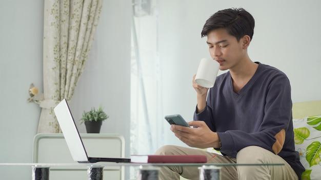 Bonito homem asiático trabalhando em casa e bebendo um copo