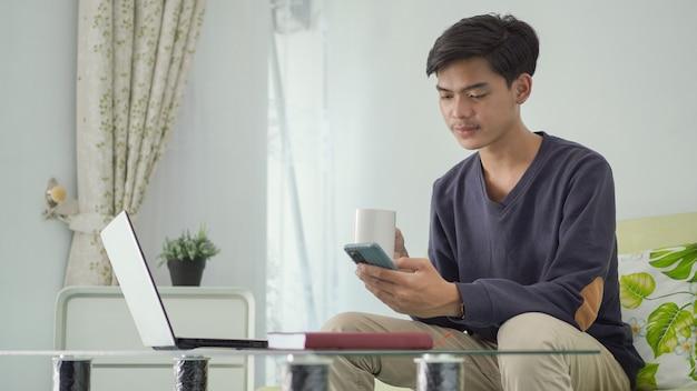Bonito homem asiático trabalhando em casa tomando um drinque