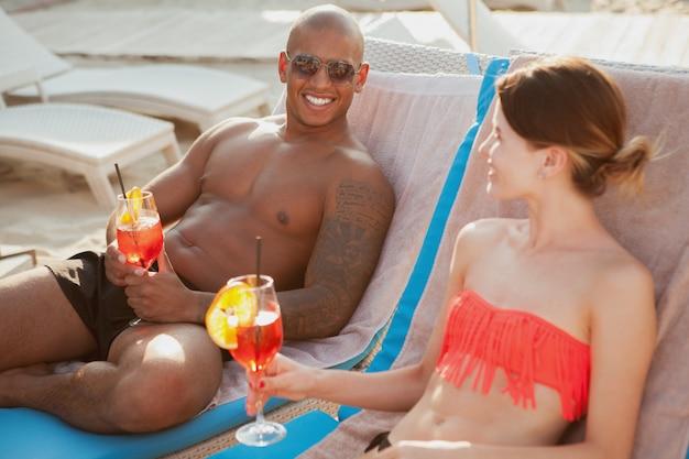 Bonito homem atlético feliz desfrutando de coquetéis com sua adorável namorada na praia. jovem casal comemorando suas férias de verão com bebidas à beira-mar