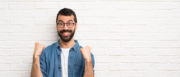 Bonito, homem barba, sobre, branca, parede tijolo, celebrando, um, vitória, em, vencedor, posição