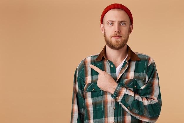Bonito homem barbudo calmo com chapéu vermelho e posando de camisa em uma parede bege