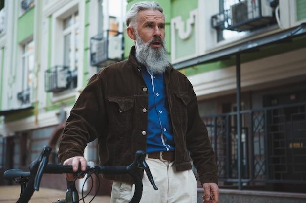 Bonito homem barbudo com cabelo grisalho andando pelas ruas da cidade com sua bicicleta