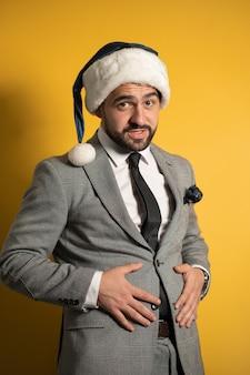 Bonito homem barbudo com chapéu de papai noel azul e terno cinza, olhando para a frente, isolado na parede amarela