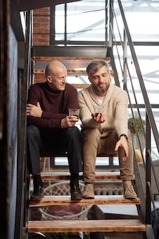 Bonito homem barbudo com copo de uísque sentado na escada e contando a história de vida com um amigo
