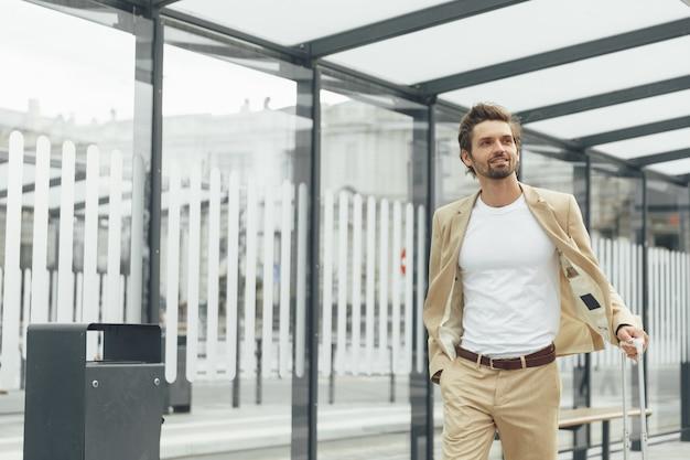 Bonito homem barbudo com roupa formal, caminhando na estação de ônibus com mala. jovem empresário em viagem de trabalho em outra cidade