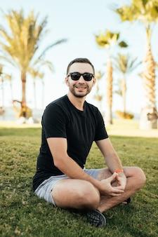 Bonito homem barbudo em óculos de sol, sentado na grama sob as palmas das mãos nas férias de verão.