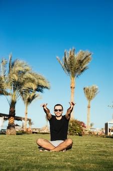 Bonito homem barbudo em óculos de sol, sentado na grama verde e relaxe, aproveite as férias de verão com as mãos levantadas, sorriso feliz.