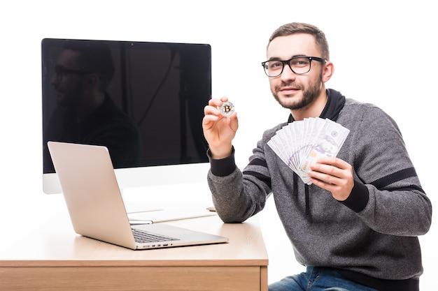 Bonito homem barbudo em seu local de trabalho com laptop e tela de monitor de pc nas costas com bitcoin e dólares em dinheiro nas mãos