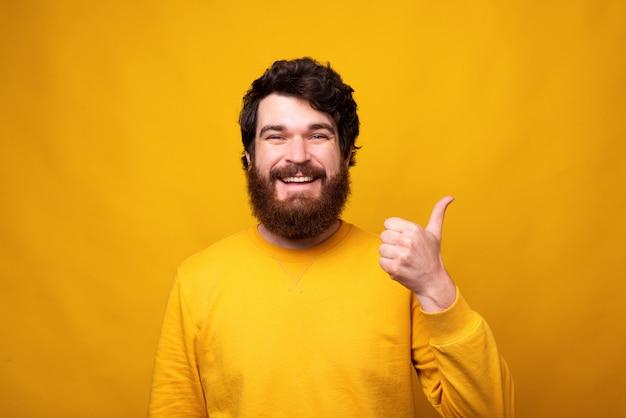 Bonito homem barbudo está aparecendo ou polegar sobre fundo amarelo.
