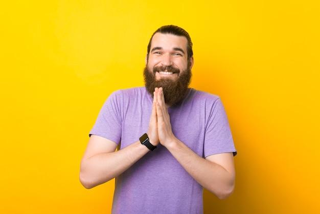 Bonito homem barbudo está desejando algo sobre fundo amarelo.
