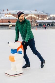 Bonito homem barbudo estar na pista de gelo, aprende a andar de skate com ajuda ou se prepara para competições de patinação