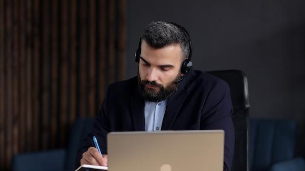 Bonito homem barbudo estudando online usando a câmera da web do laptop, escrevendo palestra no caderno. educação online, trabalho remoto, educação em casa.