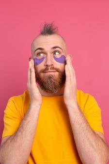 Bonito homem barbudo europeu com camiseta amarela e tapa-olhos roxos máscara rosa