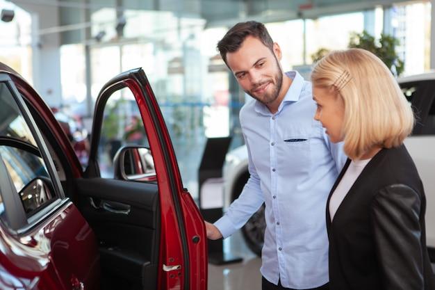 Bonito homem barbudo falando com sua esposa ao escolher o carro novo para comprar na concessionária