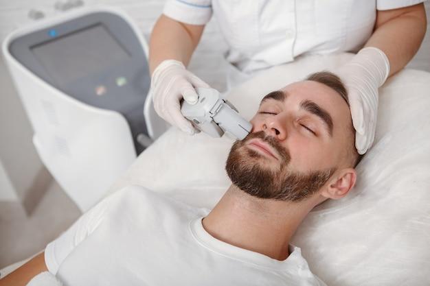 Bonito homem barbudo fazendo tratamento facial a laser com esteticista