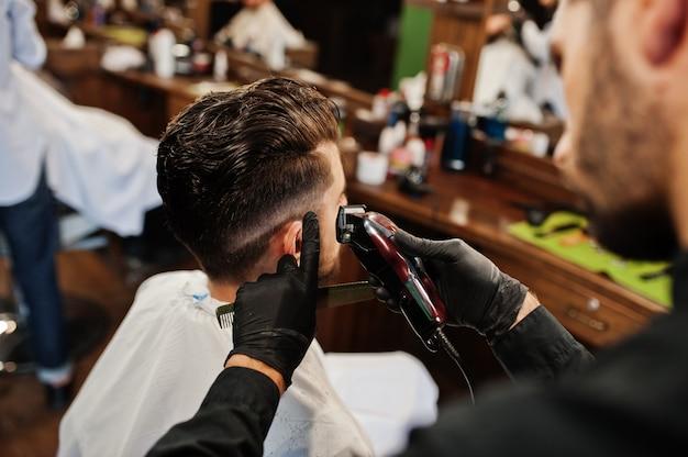 Bonito homem barbudo na barbearia, barbeiro no trabalho.
