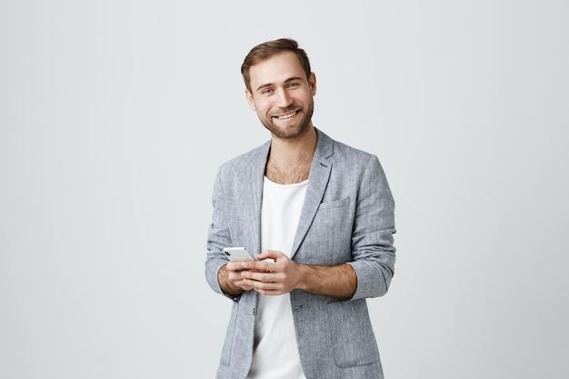 Bonito homem barbudo na jaqueta usando telefone celular