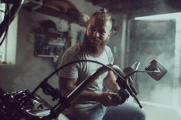 Bonito homem barbudo senta-se em um assento de moto e parece longe