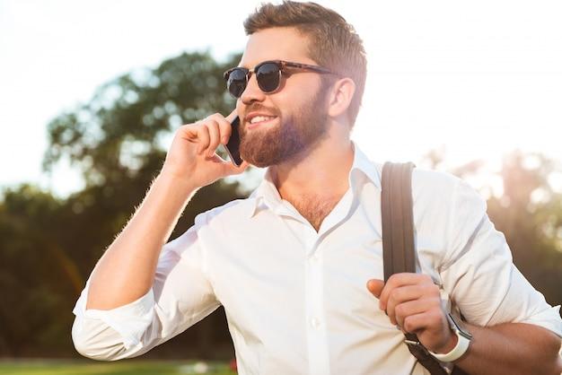 Bonito homem barbudo sorridente em óculos de sol falando pelo smartphone ao ar livre e desviar o olhar