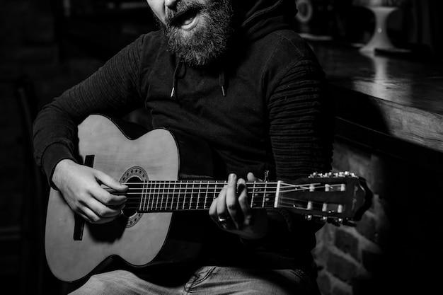 Bonito homem barbudo tocando violão no bar