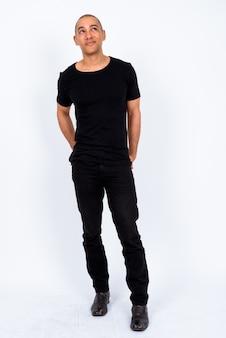 Bonito homem careca multiétnico vestindo uma camisa preta contra uma parede branca