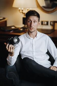 Bonito homem caucasiano está sentado na poltrona no quarto de hotel e segurando a câmera fotográfica profissional