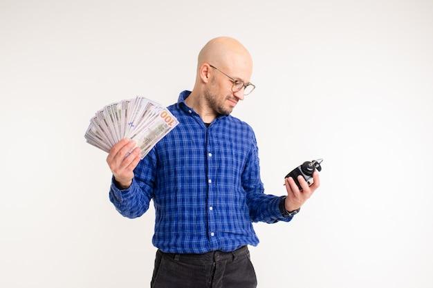 Bonito homem caucasiano sem cabelo na camisa azul, calça preta e meias azuis detém um despertador e muito dinheiro