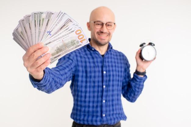 Bonito homem caucasiano sem cabelo na camisa azul, calça preta e meias azuis pensa que tempo é dinheiro