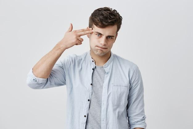 Bonito homem caucasiano sendo irritado, tem muitos problemas em casa ou no trabalho, faz gesto de suicídio, finge atirar com uma arma na cabeça, tem situação estressante na vida. conceito de depressão