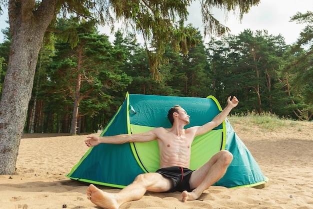 Bonito homem caucasiano sentado na areia debaixo de uma árvore perto de uma tenda verde e olhando para o lado
