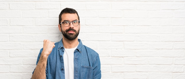 Bonito homem com barba ao longo da parede de tijolos brancos com gesto de raiva