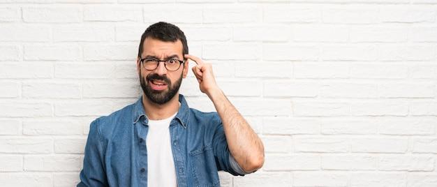 Bonito homem com barba ao longo da parede de tijolos brancos, fazendo o gesto de loucura, colocando o dedo na cabeça