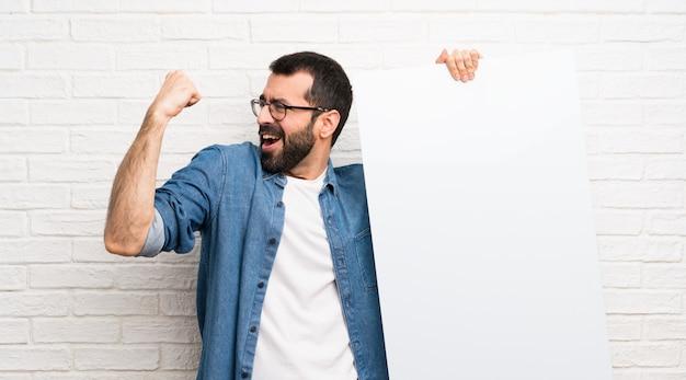 Bonito homem com barba ao longo da parede de tijolos brancos, segurando um cartaz vazio