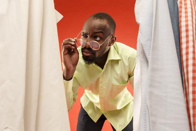 Bonito homem com barba, escolhendo a camisa em uma loja