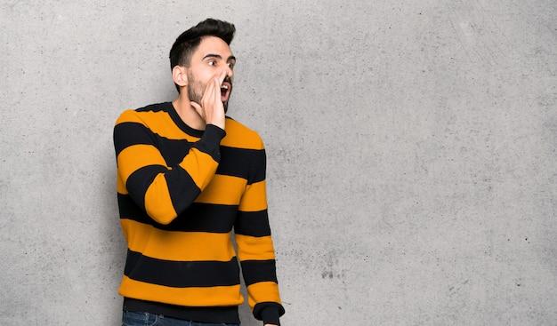 Bonito, homem, com, listrado, suéter, shouting, com, boca largo aberto, para, a, lateral, sobre, textured, parede