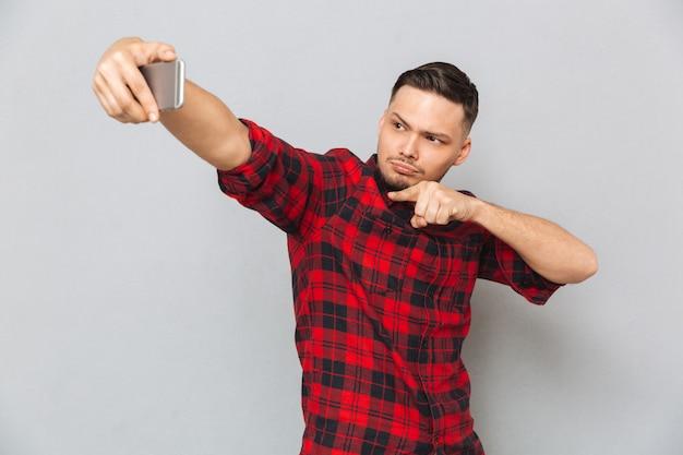 Bonito homem confiante na camisa xadrez, tendo selfie no smartphone