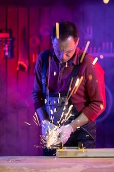 Bonito homem de meia-idade com macacão de proteção, óculos de proteção e luvas triturando metal com faíscas em metal leve colorido