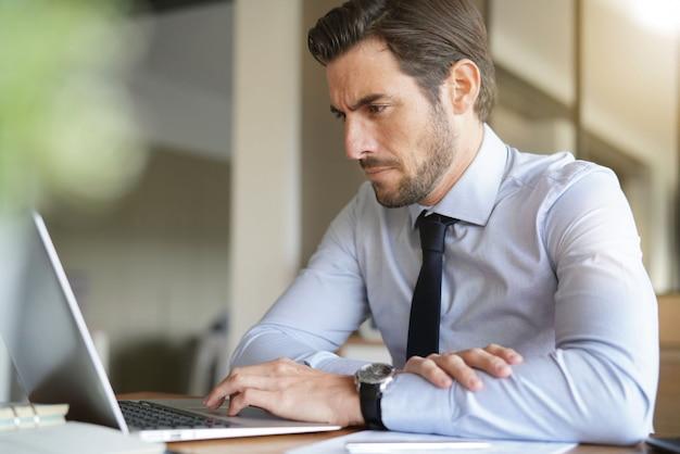 Bonito homem de negócios trabalhando no laptop no escritório moderno