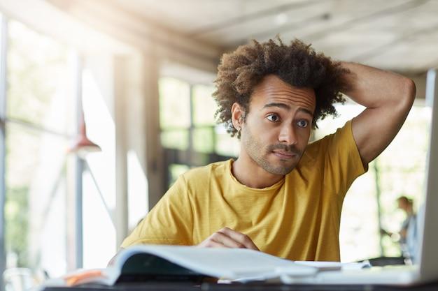 Bonito homem de pele escura, cacheado e estiloso, vestido com uma camiseta, coçando a cabeça enquanto olha para o laptop, tendo problemas para estudar