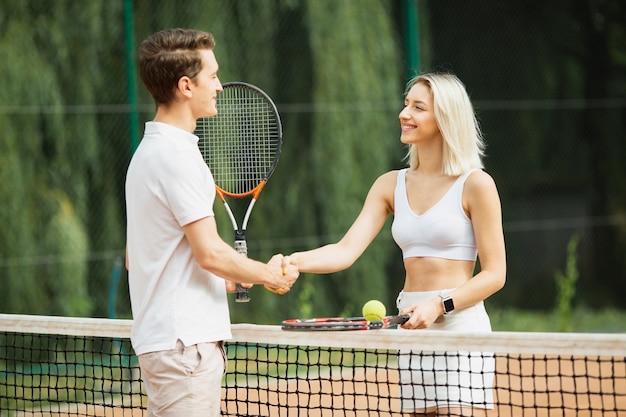Bonito homem e mulher na quadra de tênis