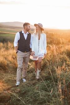Bonito homem elegante de terno rústico e boho bonita mulher de vestido, jaqueta, chapéu e botas de cowboy, andando no campo
