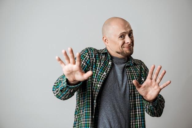 Bonito homem emocional em camisa mostrando parar sobre parede bege