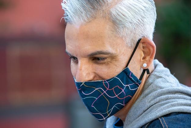 Bonito homem étnico com máscara na cidade