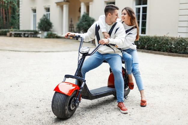 Bonito homem europeu com uma bela jovem com roupas da moda está andando de bicicleta elétrica perto do hotel. casal apaixonado
