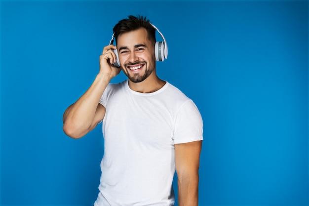 Bonito homem europeu sorri e ouve algo nos fones de ouvido