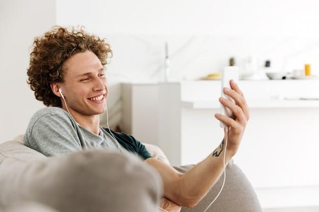 Bonito homem feliz sentado no sofá falando por telefone