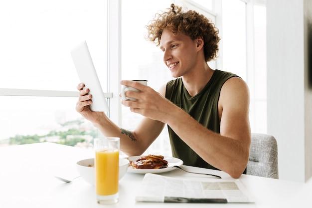 Bonito homem feliz usando computador tablet e tomando café