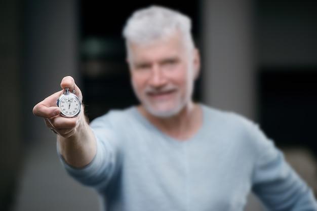 Bonito homem grisalho sênior com um cronômetro de peso na mão. conceito de esporte e saúde